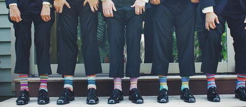 Herren in Anzügen tragen bunte Socken