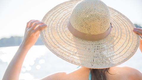 Rückansicht einer Frau im Bikini mit Strohhut an einem See.