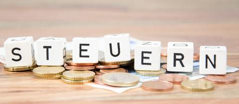 """Scrabble-Steine bilden das Wort """"Steuern"""" und liegen auf Münzgeld"""