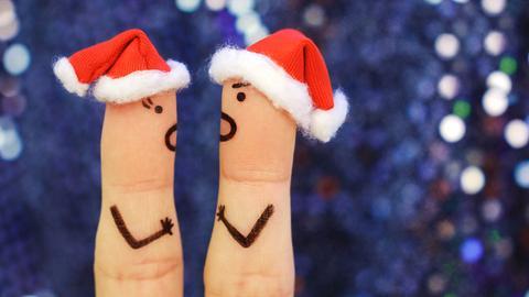 Zwei Figuren - dargestellt mit aufgemalten Gesichtern auf Fingern mit Weihnachtsmützen - streiten sich