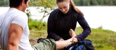 Frau verbindet den Knöchel eines Mannes