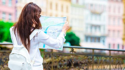Eine Frau schaut in einer fremden Stadt auf eine Karte