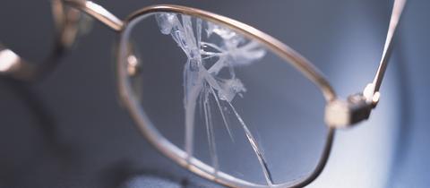 Eine kaputte Brille liegt auf einem Tisch