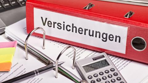 """Roter Ordner mit der Aufschrift """"Versicherungen"""""""