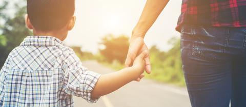 Mutter und Kind laufen Hand ind Hand auf einer Straße