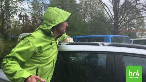 Uwe Becker wäscht im Regen ein Auto