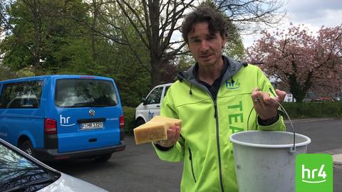 Uwe Becker beim Entfernen von Vogelkot auf der Motorhaube eines Autos
