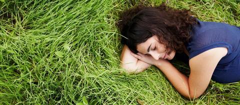 Frau liegt auf Gras