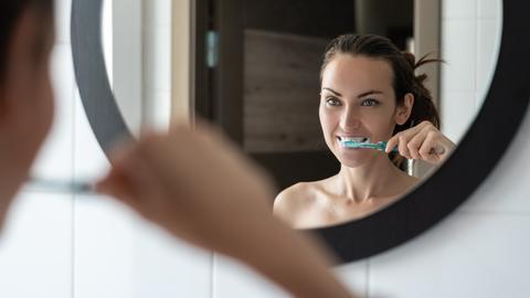 Eine Frau putzt vor dem Spiegel ihre Zähne