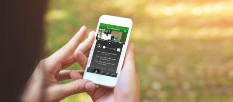 Radio hören auf dem Handy draußen in der Natur