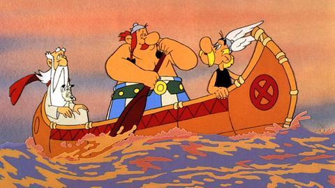 Asterix und Obelix in Amerika - die beiden paddeln in einem Kanu, Miraculix und Idefix sind mit an Bord