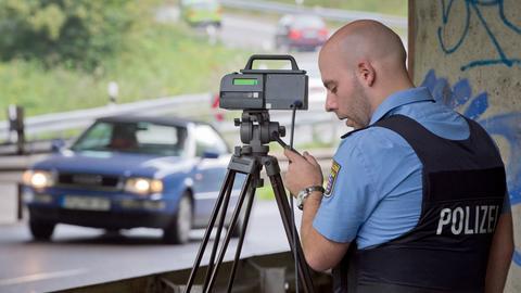 Ein Polizist mit einem Geschwindigkeitsmesser