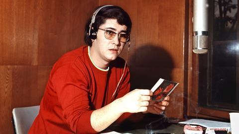"""Der Showmaster Frank Elstner sitzt während einer Sendung für """"Radio Luxemburg"""" mit Kopfhörern an einem Mikrofon."""