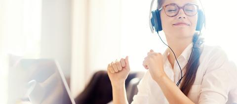 Eine junge Frau sitzt mit Kopfhörern im Büro und hört Musik
