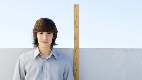 Ein Junge misst seine Größe mit einem Metermaß