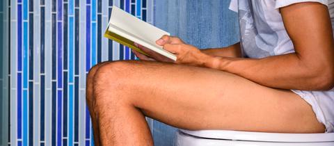 Ein Mann sitzt auf einer Toilette und liest