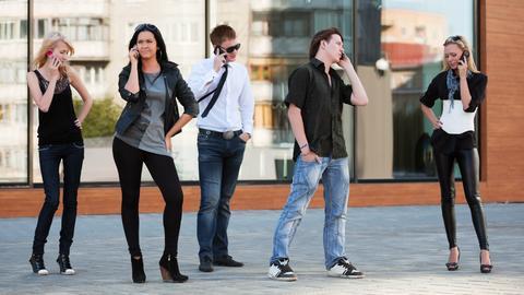 Ein Gruppe von Jugendlichen und jeder ist mit einem Smartphone am Telefonieren
